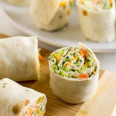 A square photo of Vegetable Tortilla Roll Ups with cream cheese filling spread on tortillas, topped with veggies and cheese. There are two roll up halves lined up on a white plate. In the foreground are three roll-ups on a wood cutting board.