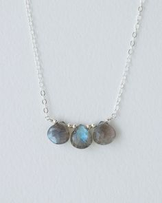 A trio of labradorite briolettes are centered on a delicate sterling silver chain. They are interspersed with tiny sterling silver beads. Necklace