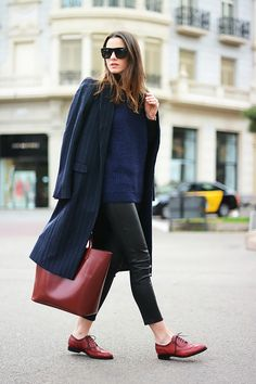 Pinstripe coat, knit sweater, leather pants, and oxfords
