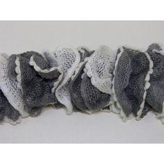 Echarpe pour femme ou adolescente tricoté a la main en laine froufrou ou fantaisie aspect petit volant avec filet très serrés et petits pompons. Elle mesure 110 cm de longueur de couleur grise & blanche avec de petits pompons blanc. Composition acrylique 80 %, nylon 20 %.