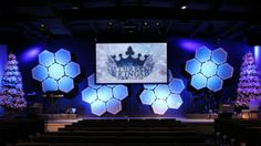 Echo Church (Full Stage) Glowing Hives.  They went to Hobby Lobby and purchased about 28 white 30″x40″ foam poster boards. Using their great math skills, a straight edge, and a table saw, they measured and cut out the hexagon shapes.