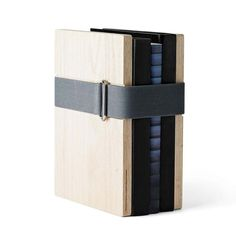 Book Binder is as simple as it is brilliant: Two end pieces of wood are fastened around your books with a big elastic band, available just a click away on The Loft Asia a luxorious lifestlye & furniture store at www.theloftasia.com
