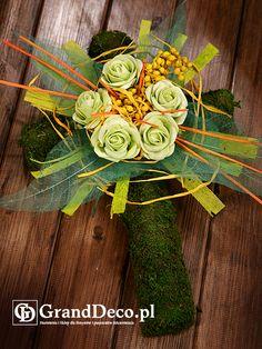 Krzyż z mchu z dekoracją z kwiatów sztucznych i suszu egzotycznego: gałązki canella farbowana na żółto, listki preparowane, ratan w paskach, papaya farbowana. Wszystkie elementy do nabycia na www.GrandDeco.pl