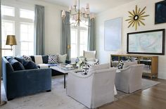 Farlane Large Chandelier illuminates a blue velvet corner sectional lined with white and blue pillows flanked by antique brass swing-arm floor lamps facing a white marble top square coffee table.