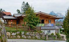 """Das """"Haus Alpenland"""" ist ein Hanghaus im Bungalow-Stil, welches durch seine Massivholzbauweise einen besonders warmen Charakter bekommt.  Malerisch gelegen an einem Südhang in Tirol wurde das wohngesunde Holzhaus optimal an die umliegende Bebauung angepasst und besticht durch die unbehandelte Lärchenholzfassade. Alle Wohnräume sind so ausgerichtet, dass sie in jeder Lage den Blick auf die umliegenden Berge freigeben. ..."""