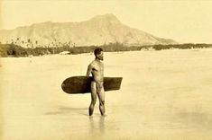 Surfer wearing traditional garb with Diamond Head in the background. Oahu, 1890. First photo ever taken of a surfer