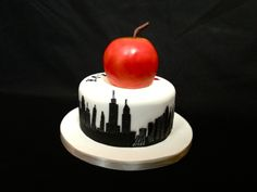 It's the Big Apple - New York Themed Birthday Cake. Victoria sponge filled with a rich white chocolate ganache.  The background buildings are airbrushed using a home made stencil. Apple is made from rice krispie treats airbrushed. Stem is modelling chocolate. #NewYork #BigApple #Cake