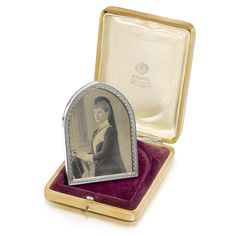 Queen Alexandra: A Fabergé silver photograph frame, workmaster Anders Nevalainen, St Petersburg, 1899-1903, of gothic arch form, the border cast with palmettes, wood back and strut inscribed in ink: 'Xmas 1904', struck with workmaster's initials and Fabergé in Cyrillic, 88 standard, partial scratched iventory number _225, containing a photograph of H.M. Queen Alexandra of Great Britain, in original Fabergé wood case.