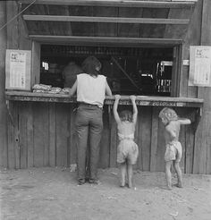 "Hop picker with her children goes from paymaster's window to adjoining company-owned store. She had earned forty-two cents that morning, spent it for one pound bologna sausage, one package ""Sensation"" cigarettes, one ""mother's cake."" Captured by Dorothea Lange. Josephine County, Oregon 1939."