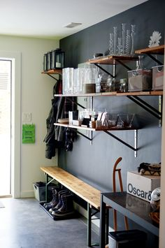 I love the dark walls and reclaimed wood shelving in this mudroom.