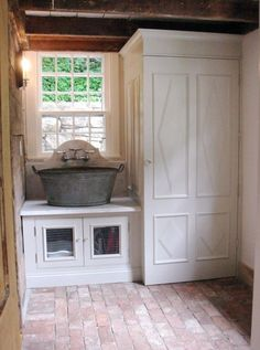 wash tub sink, washer and dryer behind cabinet, chicken wire on doors, brick floor-----love this laundry room