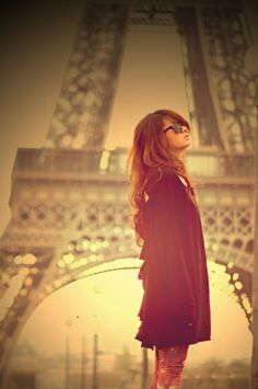 Sunset in Paris. Girl in a cardigan in front of the Eiffel tower