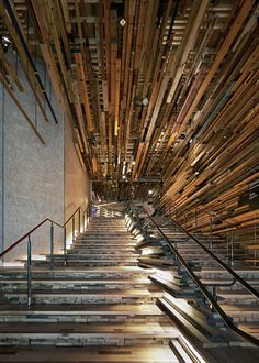 Lengths of reclaimed timber envelop the grand staircase at the entrance to Hotel Hotel in Canberra, Australia