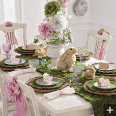 mantel blanco, camino de mesa de grama, florero de conejitos, plato plateado de base, plato de comer, servilleta fucsia con anillo plateado, rosas rosadas. / mesa aparte con torta tematica, mantel blanco, camino de mesa de grama, letrero q diga hop