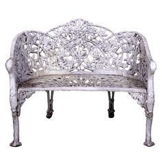 19th century Passion Flower Cast Iron Bench, old white paint, with bird heads at the arms and paw feet, with a floral carved back.