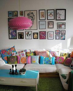 Sala bem decorada com quadros e almofadas.