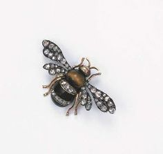 N ANTIQUE RUSSIAN BEE BROOCH The tiger's eye and onyx body with diamond line detail to the ruby eyes and rose-cut diamond wings, mounted in silver and gold, circa 1870