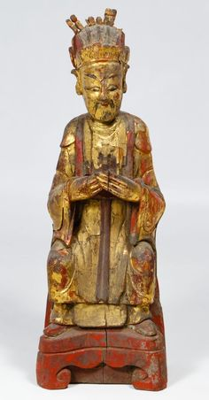 Lot 188: Asian Wood Temple Figure; 19th Century, painted gold and red male figure with his hands crossing each other; attached paper label on the underside; including COA from Hong Kong Art Craft Merchants Association