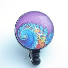 This retractable ID badge reel features a psychedelic swirl design in blues and orange on a purple background. The badge has a glass dome over it. ID Badge reels are stylish and practical. They are a