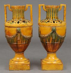 Lot 847  PAIR OF LARGE CONTINENTAL NEOCLASSICAL STYLE PROVENCIAL TWO-HANDLED GLAZED POTTERY URNS, POSSIBLY ITALIAN   Each urn pierced at the neck, decorated with fruited swags, raised on a plinth base. Provenance: Property from the Estate of George I Gravert. 37 1/2 x 12 x 12 in.