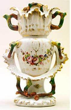 Teapot #406  Odd shape, white with entwining brown and green tree branches and bouquets of flowers on   stand, conforming pot with matching spout and handles, tree branch finial on cover.  Acquired in Vieux Paris
