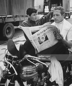 Chic barber Jay Sebring, working on actor Paul Newman's hair while he is reading the paper, sitting on motorcycle (only seat available) on the set of the film Moving Target outside sound stage at Warner Bros. Studio.