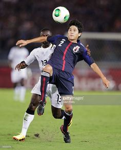 Atsuto Uchida of Japan is challenged by Frank Acheampong of Ghana during the international...