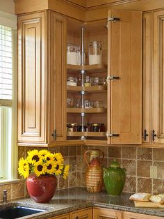 A lazy Susan maximizes corner cabinet space near the window. The basic rotating-tray idea has been around for hundreds of years, yet it remains a proven storage solution for otherwise dead-end kitchen intersections.