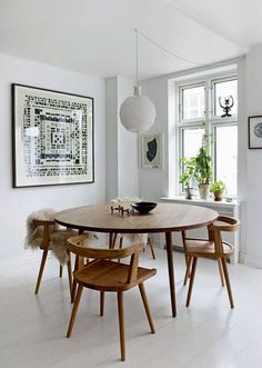 wood dining table and chairs.  beautiful pendant and love the large, tribal art!