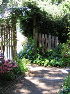A garden gate under an arbor opens onto a stone path. -- You can get more details by clicking on the image. #GardeningTips