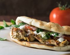 Chicken Gyros with Homemade Tzatziki Sauce features juicy marinated chicken, a slathering of fresh homemade tzatziki sauce, as well as crisp onions and tomatoes wrapped in a warm pita.