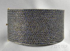 Sapphire Bracelet, designed as a tapering hinged bangle pavé-set with circular-cut sapphires, silver-gilt and black patinated mount
