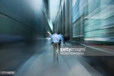 Stock Photo : Businessmen Walking Down Futuristic Passage in Financial Distric