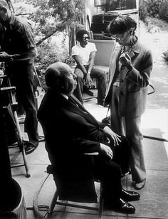 """Photo by Larry Barbier – © 1978 Larry Barbier – Image courtesy mptvimages.com  Titles: Family Plot  Names: Alfred Hitchcock, Edith Head  Characters: Silhouette at office of Vital Statistics, Man in Wheelchair at Airport  """"Family Plot,"""" Director Alfred Hitchcock with costume designer Edith Head on set. 1976 Universal"""
