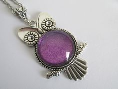 This pretty owl pendant is handmade with an antiqued silver-colored pendant, and a purple sparkly center.