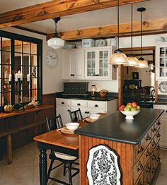 I like so much about this kitchen. The colors, the beams and white ceiling, pendant lights, island/table, interior window, paneling and more.