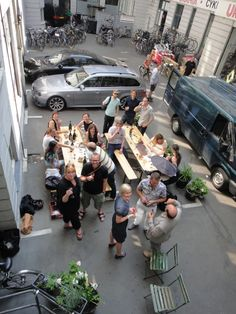 (PARK)ing Day excercise in the courtyard below Gehl Architects office, Copenhagen. Two parking spaces  were taken over with tables, benches, plants and food.