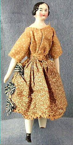 """China doll, woman, tan print dress, Germany, 1850-1863. Wisconsin Historical Society, 1945.144. """"Woman; porcelain china head, molded; black painted molded hair with center part and low molded curls; blue painted eyes... wears handmade cotton brown and white printed dress; faded lavender print flowered apron with three blue and white striped bows at right side, and rick-rack trim at hem."""""""