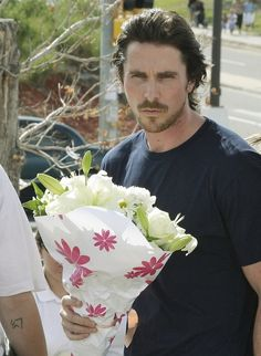 Christian Bale bringing flowers to the memorial in Aurora, Co