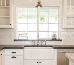 White subway tile, white cabinets, window, black countertop, farmhouse sink, lighting by Rafterhouse