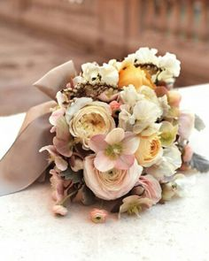 Beautiful Wedding Bouquet: Vanilla English Garden Roses, Yellow-Orange Ranunculus, Blush Ranunculus, Blush Hellebores, White Sweet Peas, White Andromeda, Dusty Miller Hand Tied With A Taupe Ribbon