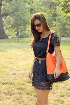 Scalloped lace dress and punchy orange bag.