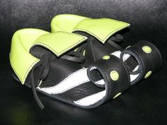 """These tiny gems are handmade from the softest black deerskin with lime green and white lambskin overlays. The lambskin lining provides warmth and comfort while allowing babies feet to breathe. They have lime green eyelets reinforcing the thong closures. The overall length is 5"""" curled x 2 """"..."""