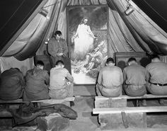 A painting depicting Christ, The Prince of Peace, consoling a battle-weary Marine, provides an appropriate background in the Korean tent, Dec. 15, 1952 where Lt. Karl Ernst leads First Division leathernecks in prayer. The painting was executed by one of the marine in the outfit. Lt. Ernst, a Protestant navy chaplain, is from McLean, Texas. (AP Photo/FW)