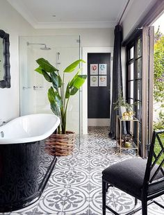Black and white bathroom features a glossy black freestanding tub atop a black and white concrete tile floor which continues into the seamless glass glass shower which is placed next to the tub.