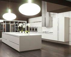 cuisine minimaliste blanche avec grand îlot et suspensions design