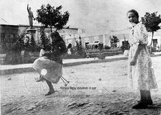 Niñas jugando con un triciclo frente a la Plaza Hidalgo,el triciclo no tiene cubierta de goma en las ruedas,del otro lado de la plaza párese ser un tranvía de mulas