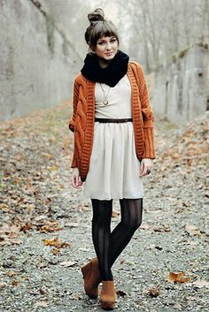 chunky black scarf, and burnt orange or mustard cabled sweater, white dress, pendant necklace, black print tights, cognac brown shoes
