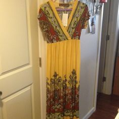 NWT Get ready for spring nice long dress NWT long yellow dress with paisley design. Dresses