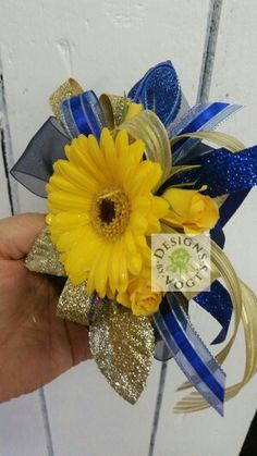 Gerbera daisy,  spray roses and glittered blue and gold ribbons create this unique Prom corsage. Unique and fresh.